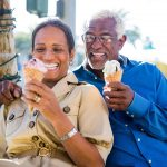 Two seniors enjoying an ice cream come in summer